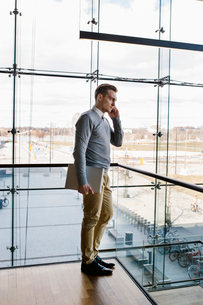 Finland, Young businessman talking on phone in office buildingの写真素材 [FYI02204206]