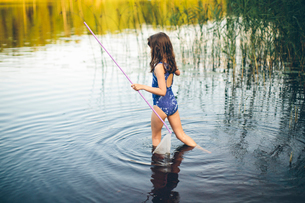 Sweden, Smaland, Mortfors, Kappemalagol, Girl (10-11) walking in water and holding poleの写真素材 [FYI02204213]