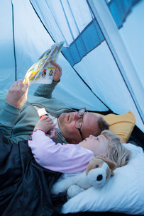 Sweden, Father and daughter (4-5) reading comic book in tentの写真素材 [FYI02204215]