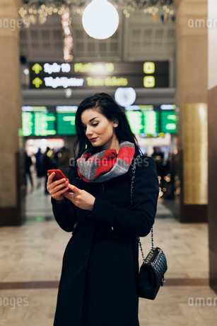 Sweden, Stockholm, Young woman using smart phone at railway stationの写真素材 [FYI02204230]