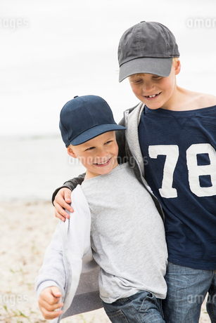 Sweden, Gotland, Smiling boys (6-7, 8-9) in baseball caps at seashoreの写真素材 [FYI02204245]