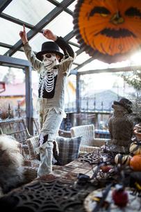 Finland, Boy (8-9) wearing skeleton costume raising arms in houseの写真素材 [FYI02204295]