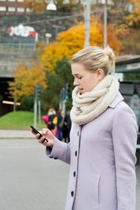Sweden, Vastra Gotaland, Gothenburg, Young woman wearing overcoat using smart phone in streetの写真素材 [FYI02204313]