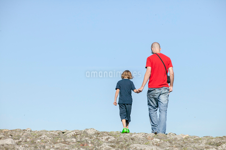 Sweden, Skane, Osterlen, Father with son (14-15) holding handsの写真素材 [FYI02204315]