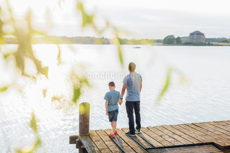 Sweden, Blekinge, Karlskrona, Father and son (8-9) by lakeの写真素材 [FYI02204318]
