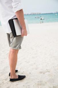 United Arab Emirates, Dubai, Mature man standing on beach and holding laptopの写真素材 [FYI02204319]