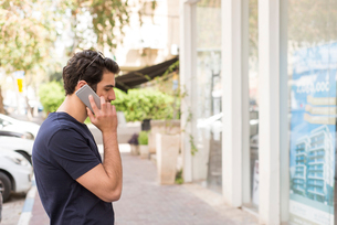Israel, Man talking on phone in front of buildingの写真素材 [FYI02204333]