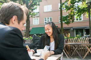Sweden, Skane, Malmo, Man and woman drinking coffee and using smartphones in sidewalk cafeの写真素材 [FYI02204338]