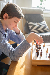Sweden, Boy (12-13) playing chess in living roomの写真素材 [FYI02204341]