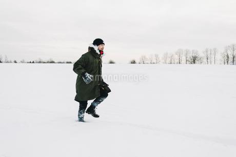Sweden, Smaland, Teleborg, Man walking in snowy fieldの写真素材 [FYI02204354]