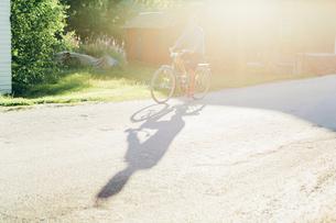 Sweden, Smaland, Mortfors, Man cycling on roadの写真素材 [FYI02204380]