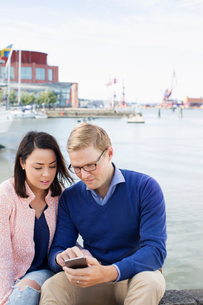 Sweden, Vastergotland, Gothenburg, Young couple sitting by harbor and checking smart phoneの写真素材 [FYI02204385]