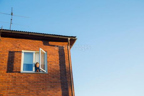 Sweden, Boy (14-15) looking through window of brick houseの写真素材 [FYI02204420]