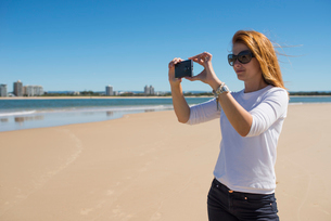 Australia, Queensland, Sunshine Coast, Maroochydore, Pincushion Island, Mid adult woman taking pictuの写真素材 [FYI02204426]