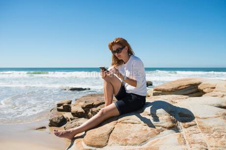 Australia, Queensland, Sunshine Coast, Maroochydore, Pincushion Island, Woman sitting on rock at seaの写真素材 [FYI02204444]