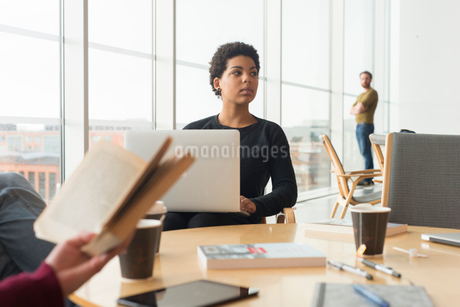 Sweden, Woman sitting at table and holding laptopの写真素材 [FYI02204449]