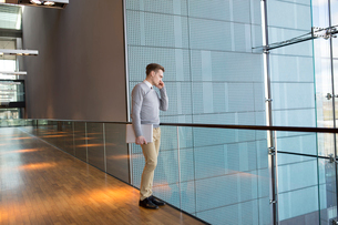 Finland, Young businessman talking on phone in office buildingの写真素材 [FYI02204452]