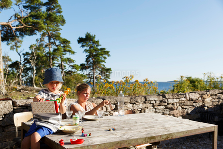 Sweden, Gotland, Bungenas, Mother and daughter (2-3) sitting at table outdoorsの写真素材 [FYI02204463]
