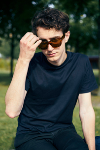 Sweden, Uppland, Man in black and sunglasses sitting in parkの写真素材 [FYI02204467]