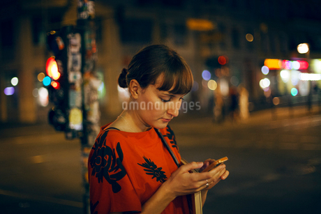 Germany, Berlin, Beautiful woman texting in city at nightの写真素材 [FYI02204477]