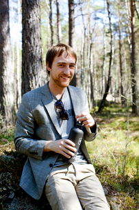 Sweden, Uppland, Smiling man sitting on grass and holding insulated drink containerの写真素材 [FYI02204489]