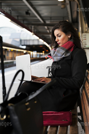 Sweden, Stockholm, Young woman sitting at railroad stationの写真素材 [FYI02204508]