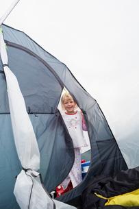 Sweden, Smiling girl (4-5) in pajamas standing in grey tentの写真素材 [FYI02204515]
