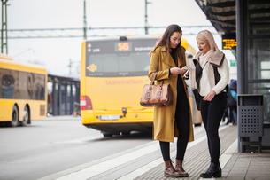 Sweden, Skane, Kirstianstad, Two young women standing with smartphones at bus stationの写真素材 [FYI02204558]