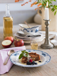 Sweden, Apple crumble with custard on dining tableの写真素材 [FYI02204576]