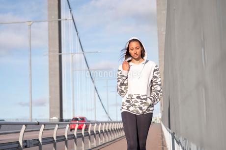 Sweden, Vastergotland, Gothenburg, Young woman standing on sidewalk of bridgeの写真素材 [FYI02204579]
