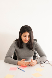 Israel, Young woman with mobile phone sitting in officeの写真素材 [FYI02204610]