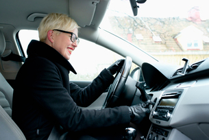 Sweden, Sodermanland, Stockholm, Blonde woman on driver´s seat starting carの写真素材 [FYI02204620]