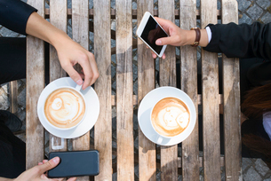 Sweden, Man and woman drinking coffee in sidewalk cafeの写真素材 [FYI02204623]
