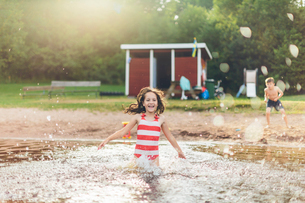 Sweden, Smaland, Mortfors, Kappemalagol, Girl (8-9) splashing water and boy (6-7) standing on groundの写真素材 [FYI02204640]