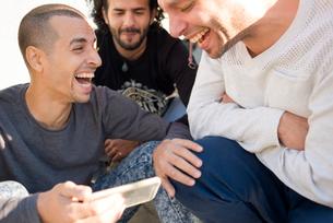 Israel, Tel Aviv, Men crouching and laughingの写真素材 [FYI02204644]