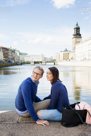 Sweden, Vastergotland, Gothenburg, Young couple sitting on promenade by canalの写真素材 [FYI02204689]