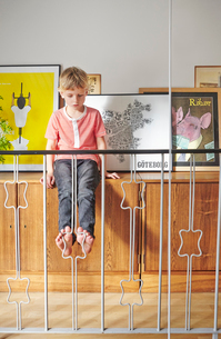 Sweden, Boy sitting on cupboard with pictures behind railingの写真素材 [FYI02204707]