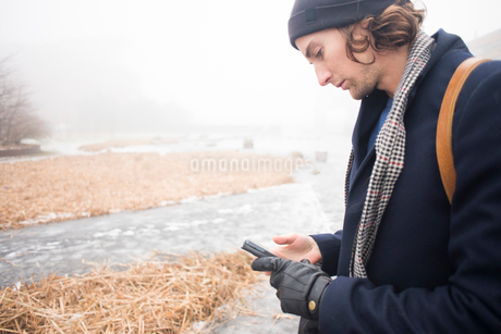 Sweden, Skane, Malmo, Man using mobile phone by riverの写真素材 [FYI02204709]