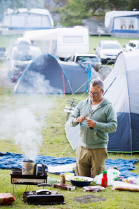 Sweden, Bohuslan, Marstrand, Koon, Mature man cooking at campsiteの写真素材 [FYI02204710]