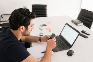Israel, Man sitting in office and using mobile phone and laptopの写真素材 [FYI02204711]