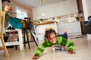 Sweden, Girl (6-7) lying on skateboard on kitchen floorの写真素材 [FYI02204713]