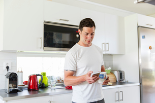 Sweden, Man using mobile phone in kitchenの写真素材 [FYI02204724]