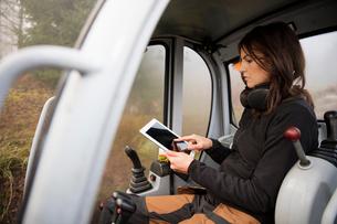 Sweden, Uppland, Nacka, Woman using digital tablet in bulldozerの写真素材 [FYI02204738]