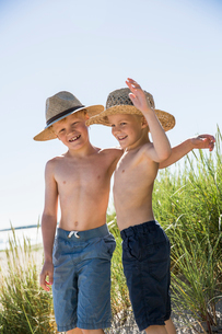 Sweden, Gotland, Shirtless boys (6-7, 8-9) in straw hats standing on dune at seashoreの写真素材 [FYI02204780]