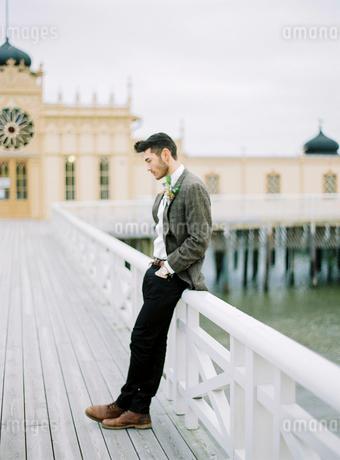 Sweden, Halland, Varberg, Groom wearing tuxedo leaning against railing on pierの写真素材 [FYI02204782]