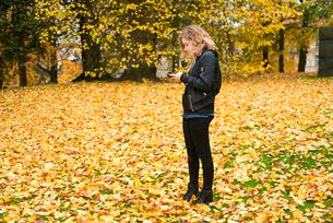 Sweden, Vastergotland, Gothenburg, Girl (16-17) using mobile phone in parkの写真素材 [FYI02204789]