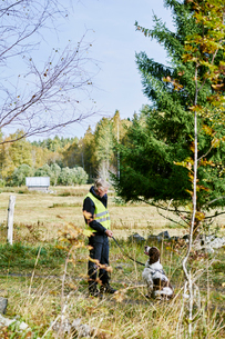 Sweden, Uppland, Rison, Volunteer with dog helping emergency services find missing peopleの写真素材 [FYI02204816]