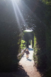 Sweden, Skane, Girl (2-3) running in garden alleyの写真素材 [FYI02204836]
