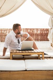 United Arab Emirates, Dubai, Mature man sitting on mattress on terrace under canopy and using laptopの写真素材 [FYI02204839]