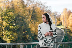 Sweden, Vastergotland, Gothenburg, Young woman listening to music on smart phoneの写真素材 [FYI02204842]